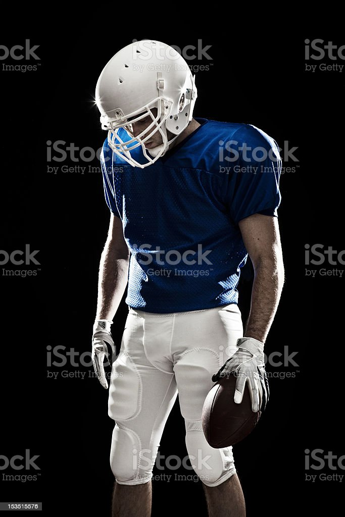 Football player with ball in the hand, looking down as if he were...