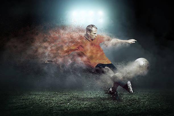 Football player with ball around splash drops on the stadium stock photo