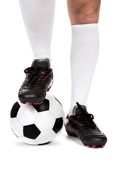 Football player with ball on white Legs of soccer player with ball on white background studded stock pictures, royalty-free photos & images