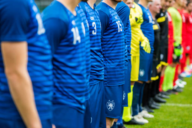 football players and referees standng in line at start of match - national anthem stock photos and pictures