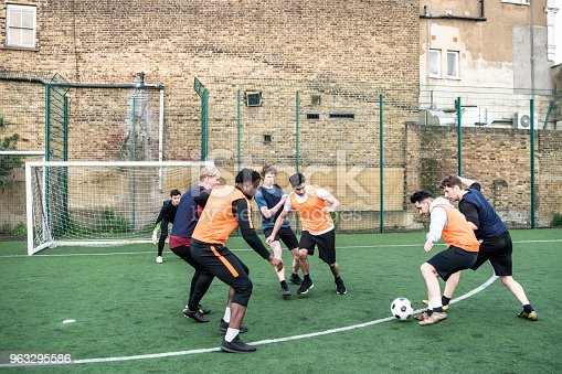 istock Football players approaching the goal with young man tackling his opponent 963295586