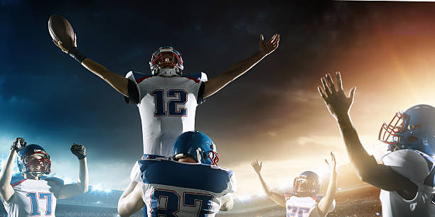 Football Players celebrate their victory Group of tough American football players celebrating their victory. They are expressing their emotions freely.  The action takes place on professional stadium. Players wear unbranded sports uniform. quarterback stock pictures, royalty-free photos & images
