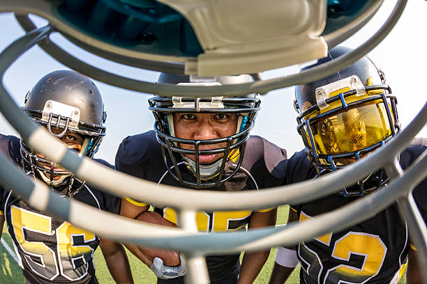 Football Players Get in Each Others Faces Three opposing football players get in the face of a football player line of scrimmage stock pictures, royalty-free photos & images