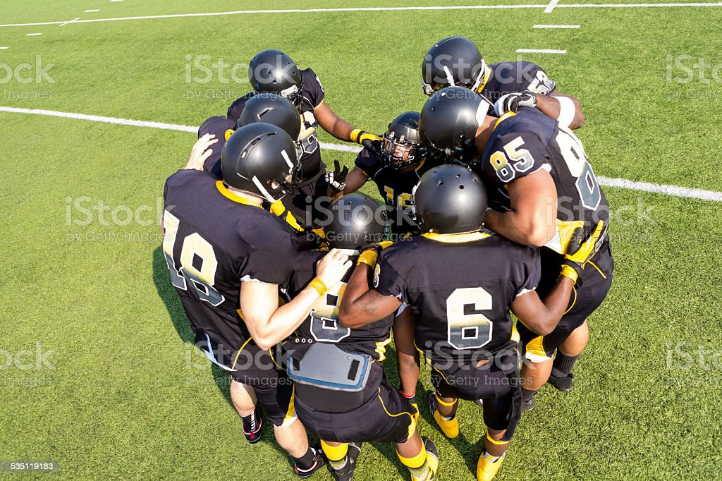 Football players huddled together before play on field stock photo