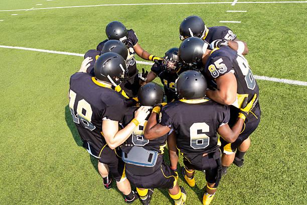joueurs de foot huddled ensemble avant le jeu sur terrain - se regrouper photos et images de collection