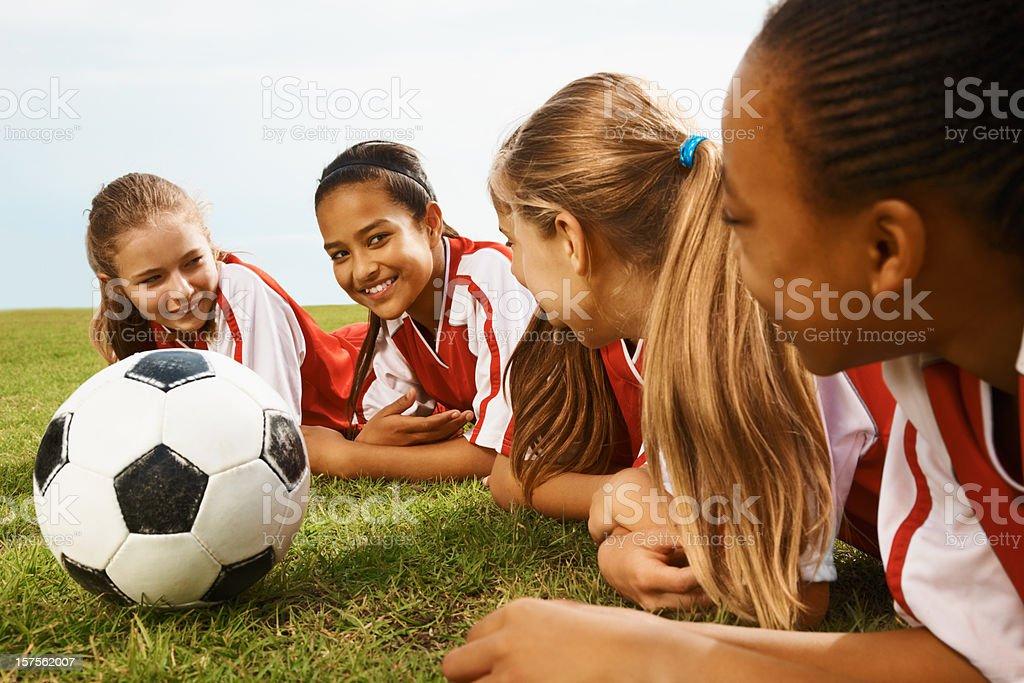 Football players lying on grass stock photo