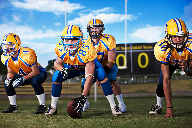 Football players preparing to play football  line of scrimmage stock pictures, royalty-free photos & images
