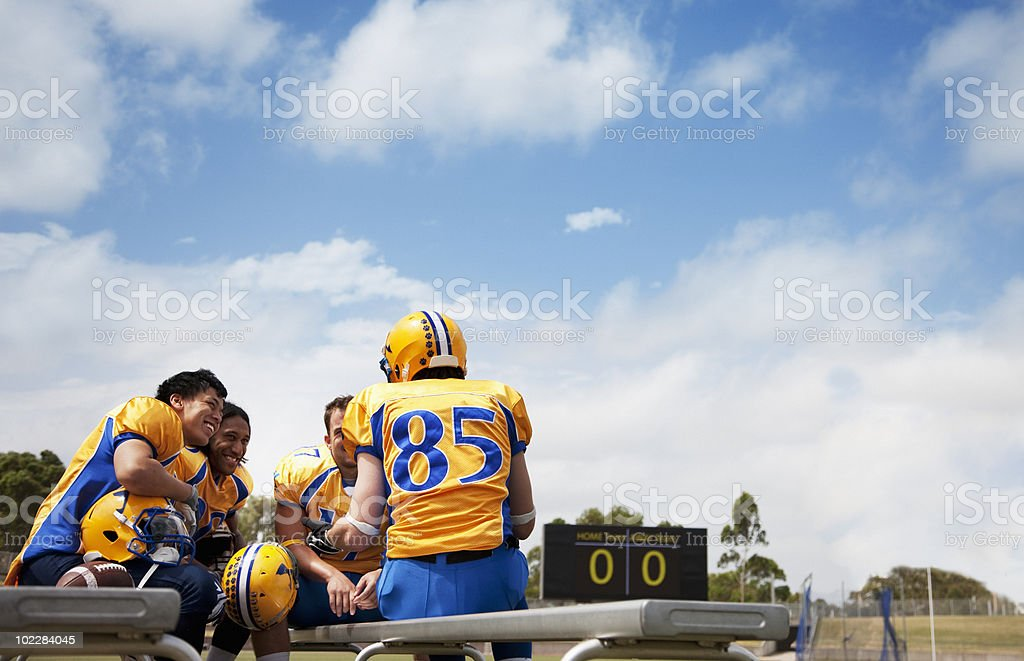 Football players resting on bench stock photo