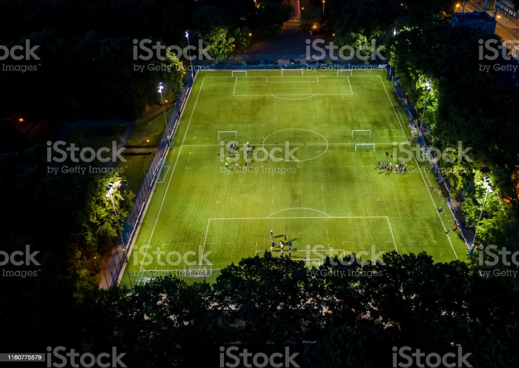 Football players running around the football field. Night workout....