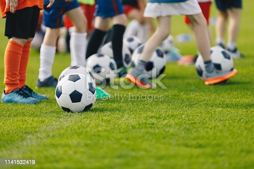 istock Football practice for youth. Children soccer training background. Group of young boys training soccer drills on green grass. 1141532419