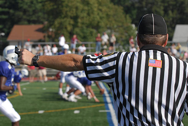 Football Referee A referee at a North American Football game.  He has his arm extended his whistle and stop watch are visible.  There is an active game with players and spectators in the blurred background referee stock pictures, royalty-free photos & images