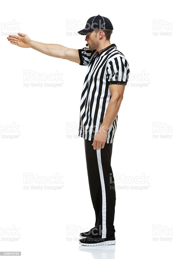 Football referee whistling & showing fist down stock photo
