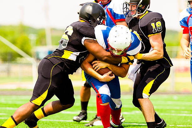 Football running back being tackled A football player is running with the ball in his arms.  He is holding the ball tight, while two players from the other team are trying to take it.  The man with the ball is dressed in a blue and white uniform.  The other team's uniform is black and yellow. wide receiver athlete stock pictures, royalty-free photos & images