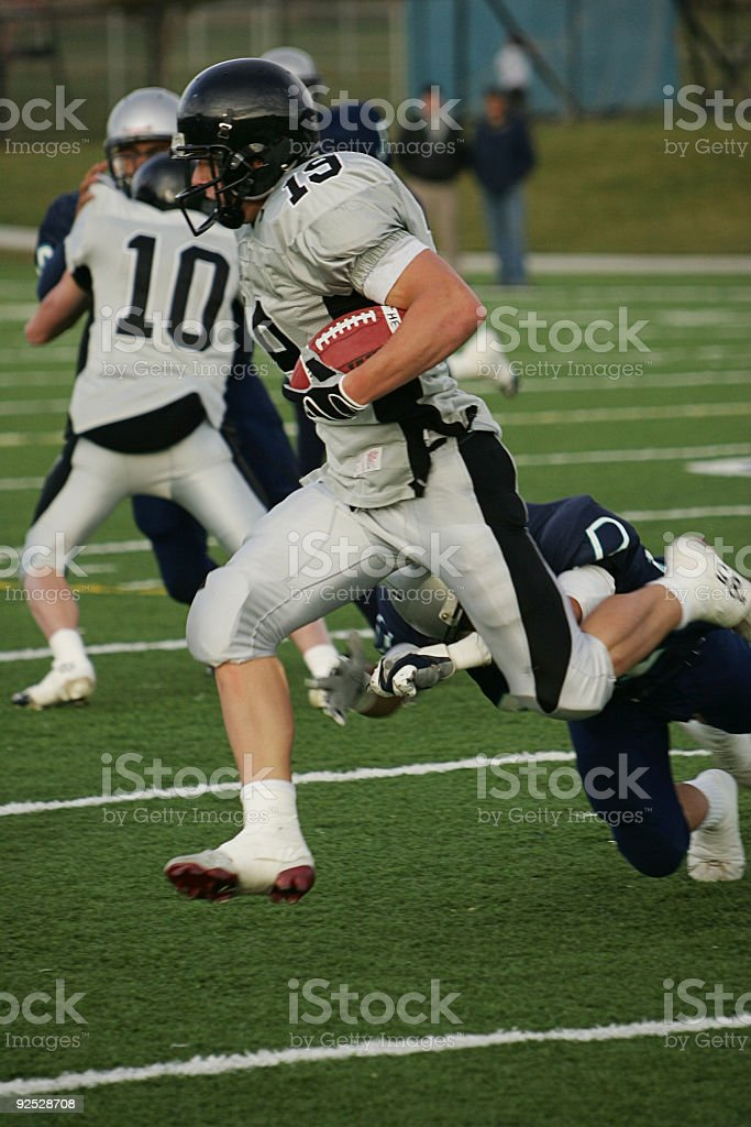 Football Running Back Carries Ball for Big Gain stock photo