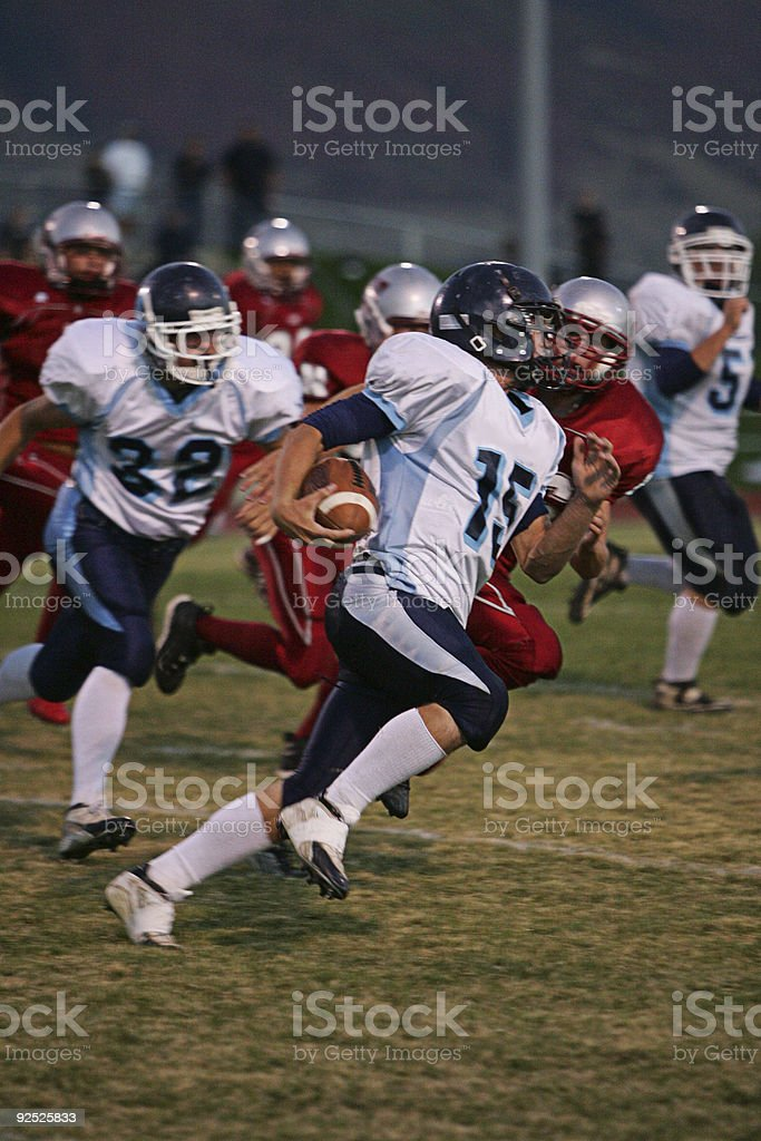 Football Running Back Runs Ball Around End stock photo