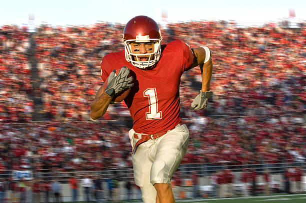 football running back sprinting down the field - american football player stock photos and pictures