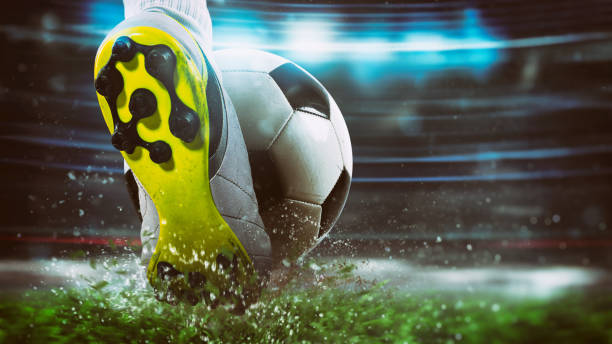 Football scene at night match with close up of a soccer shoe hitting the ball with power - foto stock