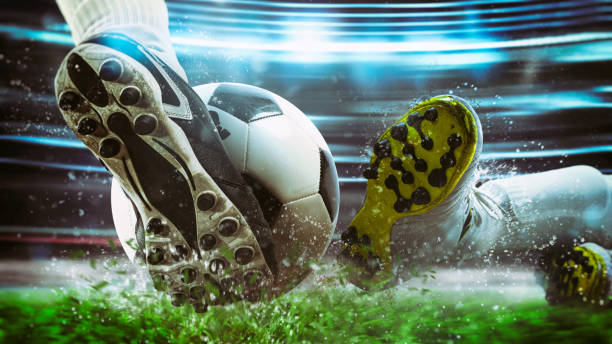 football scene at night match with close up of a soccer shoe hitting the ball with power - footbal стоковые фото и изображения