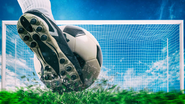 Football scene at night match with close up of a soccer shoe hitting the ball with power stock photo