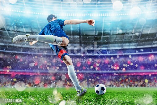 istock Football scene at night match with player kicking the ball with power 1155511506