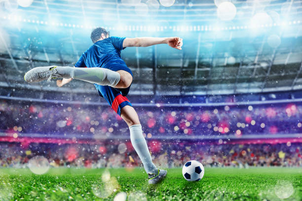 Football scene at night match with player kicking the ball with power - foto stock