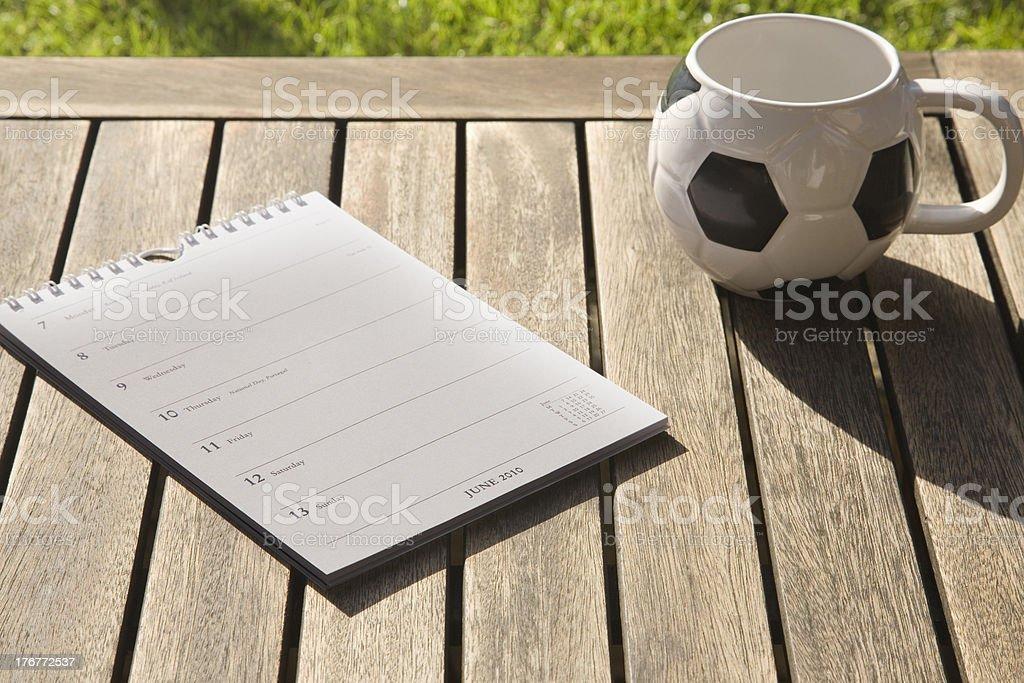 A Football shaped coffee mug and a 2010 Calendar showing royalty-free stock photo