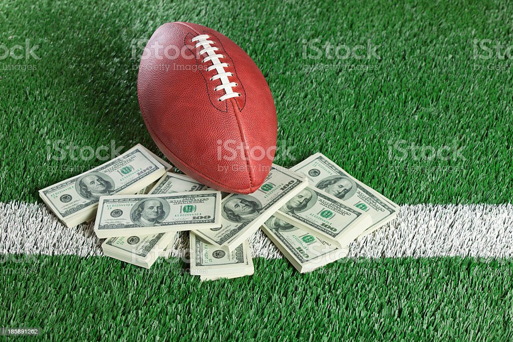 NFL football sitting with piles of dollars on AstroTurf stock photo
