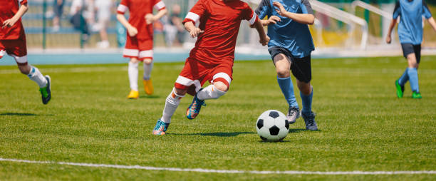 football soccer joueurs en cours d'exécution avec la balle. footballeurs kicking football match. les jeunes footballeurs courent après le bal. enfants en uniformes de soccer rouge et bleu. stade de football en arrière-plan - football photos et images de collection