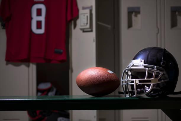 Football sports equipment in school gymnasium locker room. stock photo