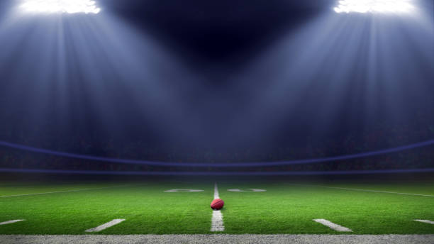 Football stadium American football field illuminated by stadium lights american football field stock pictures, royalty-free photos & images