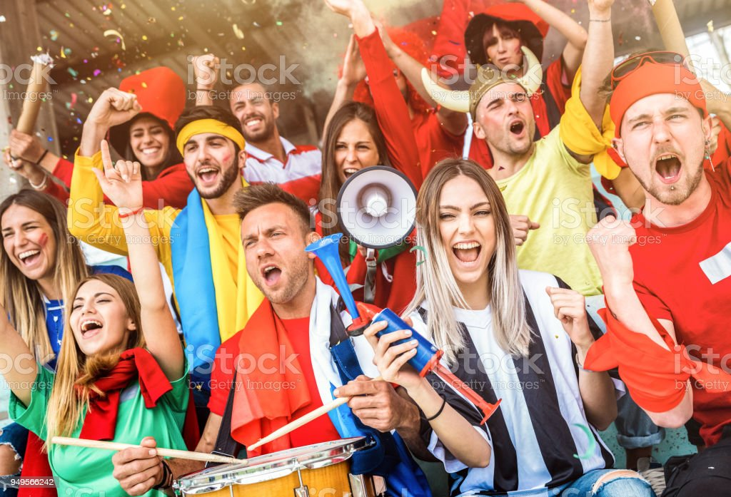 Football supporter fans friends cheering and watching soccer cup match at intenational stadium - Young people group with multicolored t-shirts having excited fun on sport world championship concept royalty-free stock photo