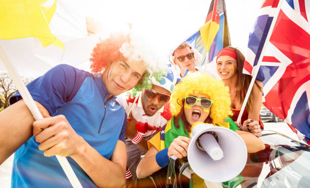 Football supporter fans friends taking selfie after soccer match hanging around together - Young people group with multicolored t-shirts and wigs having excited fun. stock photo
