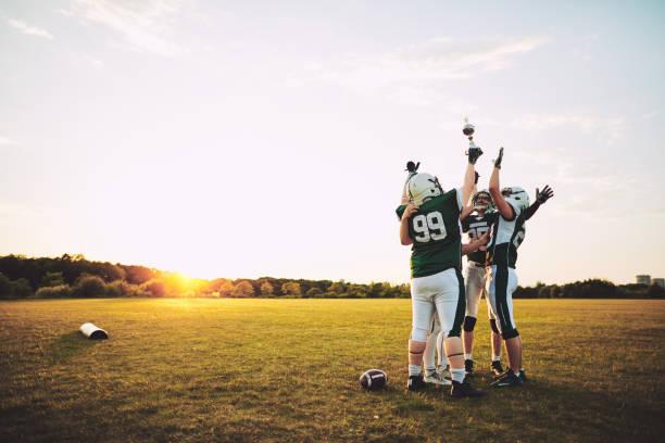 team van de voetbal vieren met hun kampioenschap trofee op een veld - samen sporten stockfoto's en -beelden