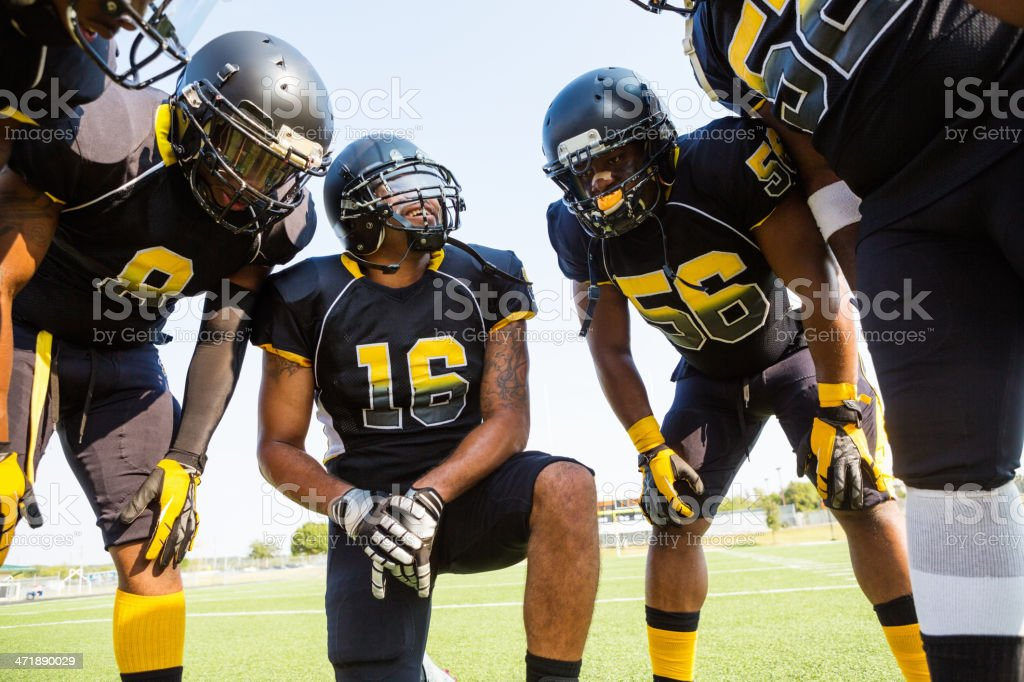 Football team discussing strategy during game stock photo