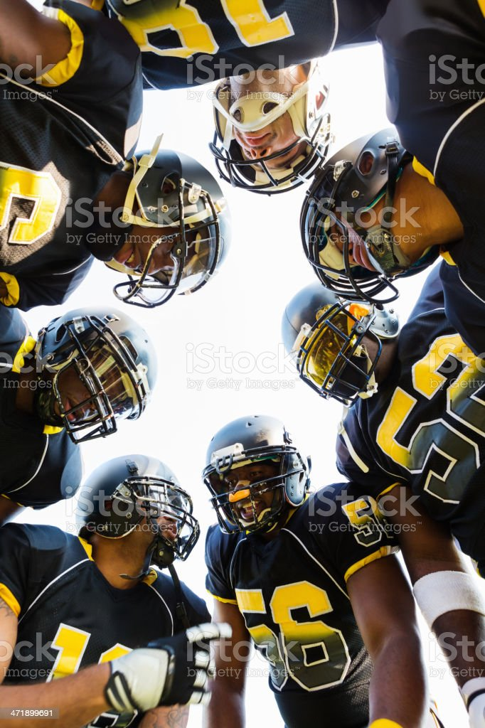 Football team huddling together during game time out stock photo