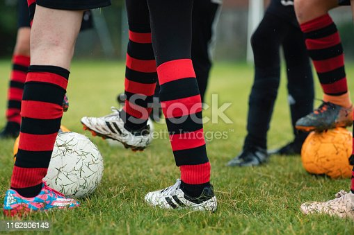 A low angle view of a group of teenagers wearing their football team uniform, ready to play football.