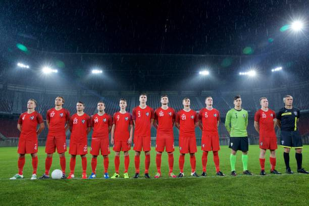 football team standing in a row - national anthem stock photos and pictures