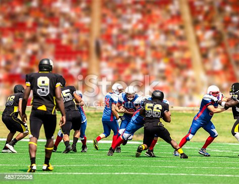 istock Football team's running back carries ball. Defenders. Stadium fans. Field. 483722258