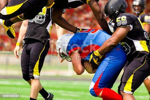 istock Football team's running back carries ball. Defenders. Stadium fans. Field. 536506335