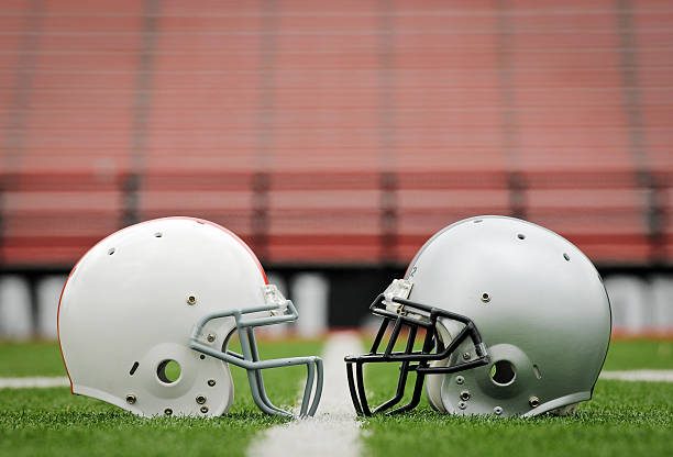 Football The Big Game Stock photo of to football helmets sitting face to face on field football helmet stock pictures, royalty-free photos & images