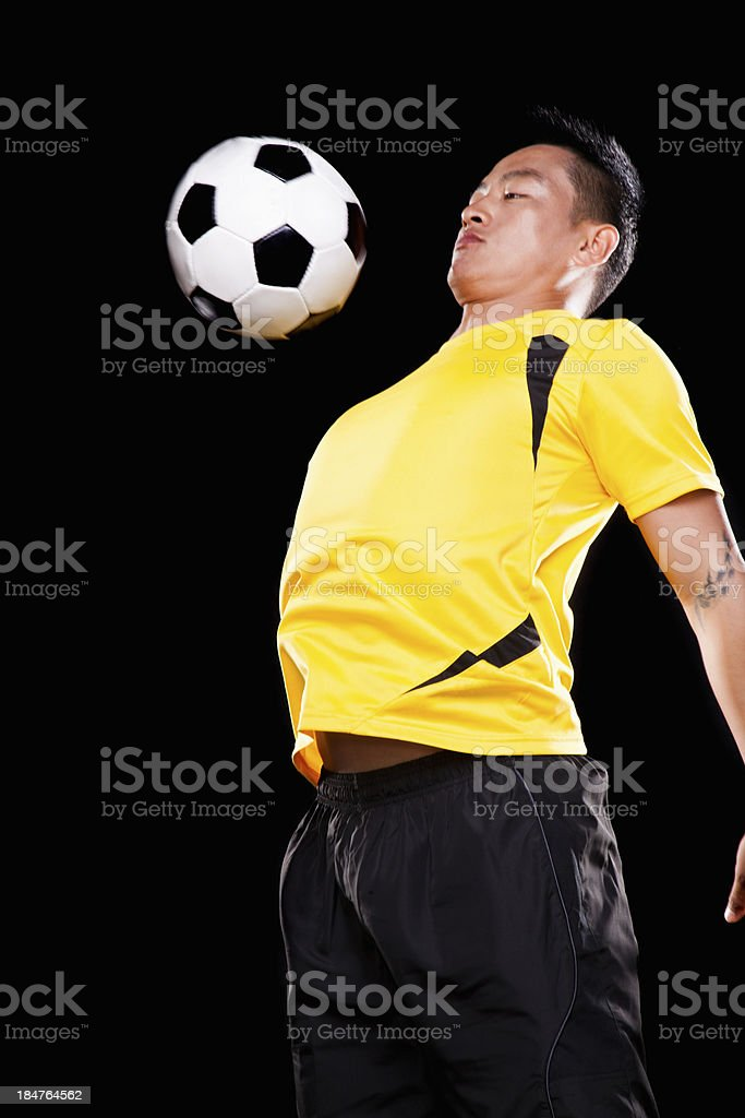Footballer chesting ball, black background royalty-free stock photo