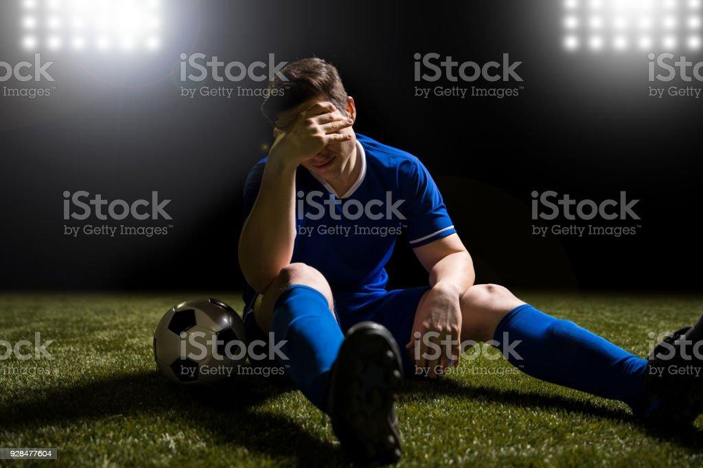 Estar decepcionado de futbolista en el campo de hierba - foto de stock