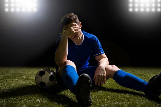 Footballeur déçue assis sur le terrain avec gazon - Photo