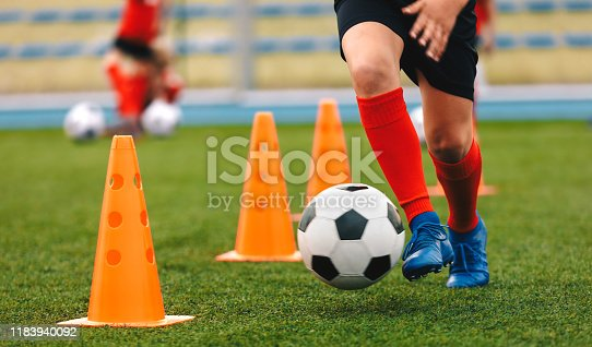 istock Footballer dribbling ball on training between orange cones. Young football player in sports blue cleats and red socks 1183940092