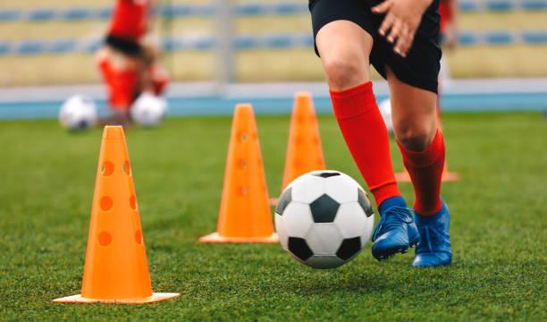 voetballer dribbelen bal op training tussen oranje kegels. jonge voetbalspeler in sport blauwe schoenplaatjes en rode sokken - sport stockfoto's en -beelden