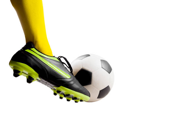 footballer feet kicking soccer ball stock photo