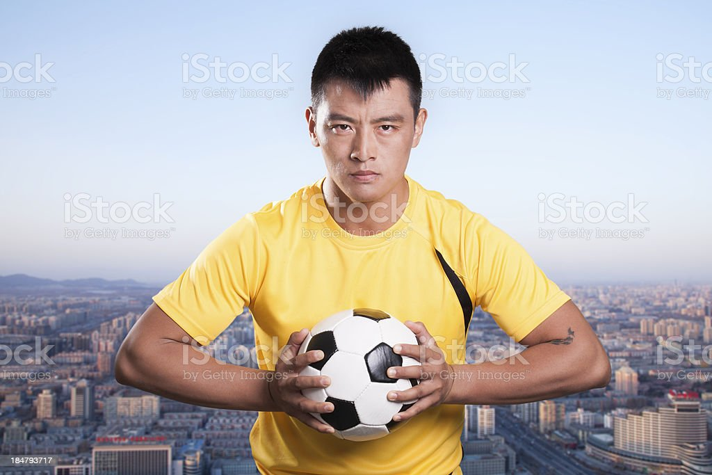 Footballer holding ball to chest, cityscape background royalty-free stock photo