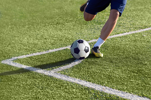 Footballer is preparing to give a corner kick with the ball on the goal on the green grass, playing on the football field.