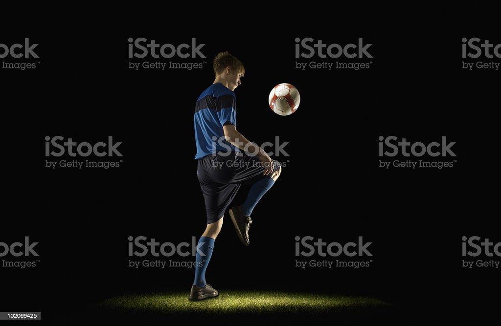 Footballer keeping ball up royalty-free stock photo
