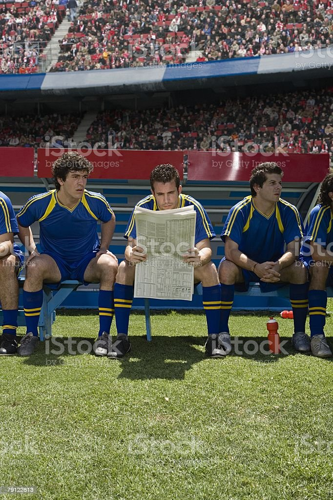Footballer reading a newspaper royalty-free stock photo